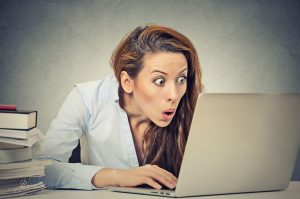 cropped-shocked-business-woman-sitting-in-front-of-laptop-computer-49549881.jpg